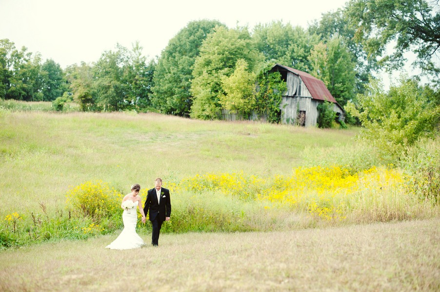 Bride and groom walking in front of an old barn