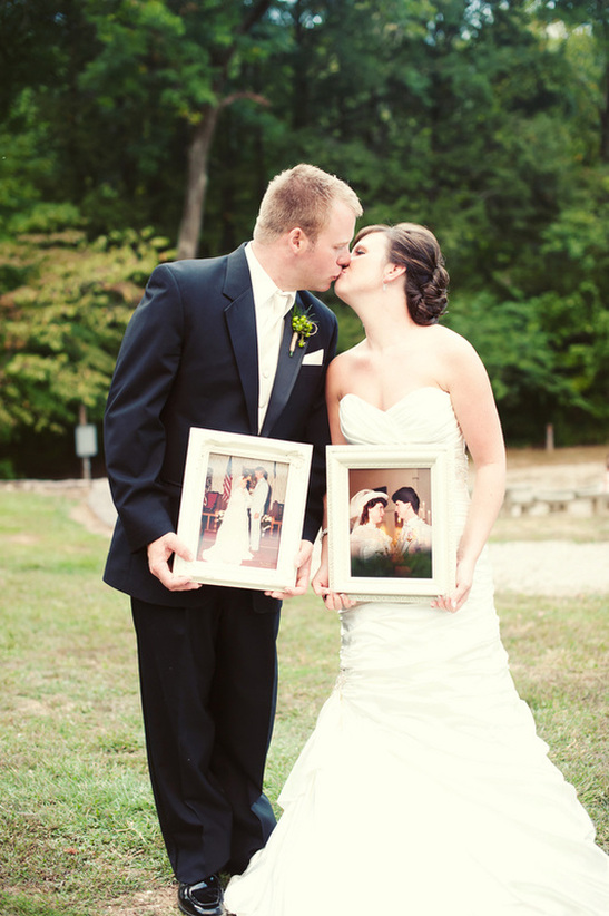 Bride and groom kissing and holding pictures of parents